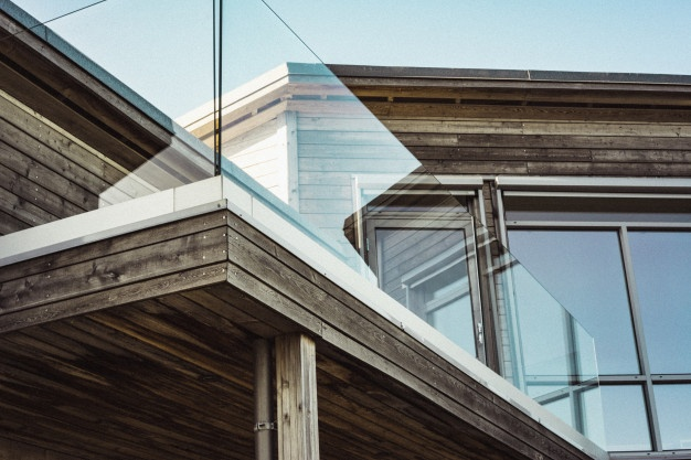 low-angle-shot-modern-wooden-house-with-glass-terrace-borders_181624-5142